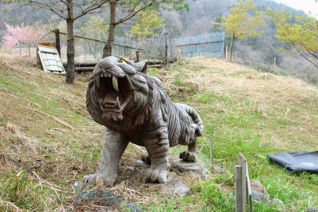 Tiger carved wooden statue at entrance to the senbonzakura of Torayama